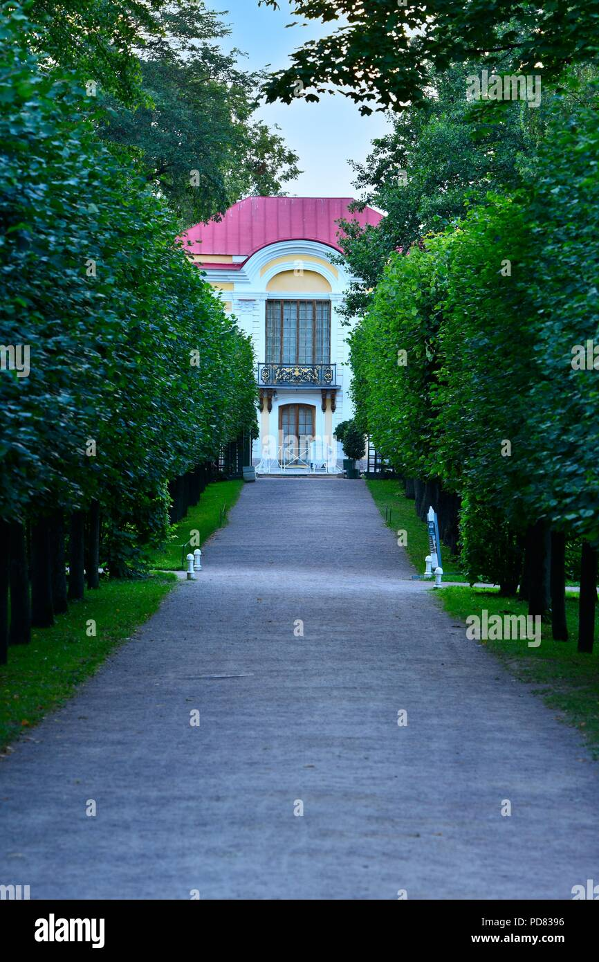 An alley of trees toward a white garden building with redish roof - Stock Image