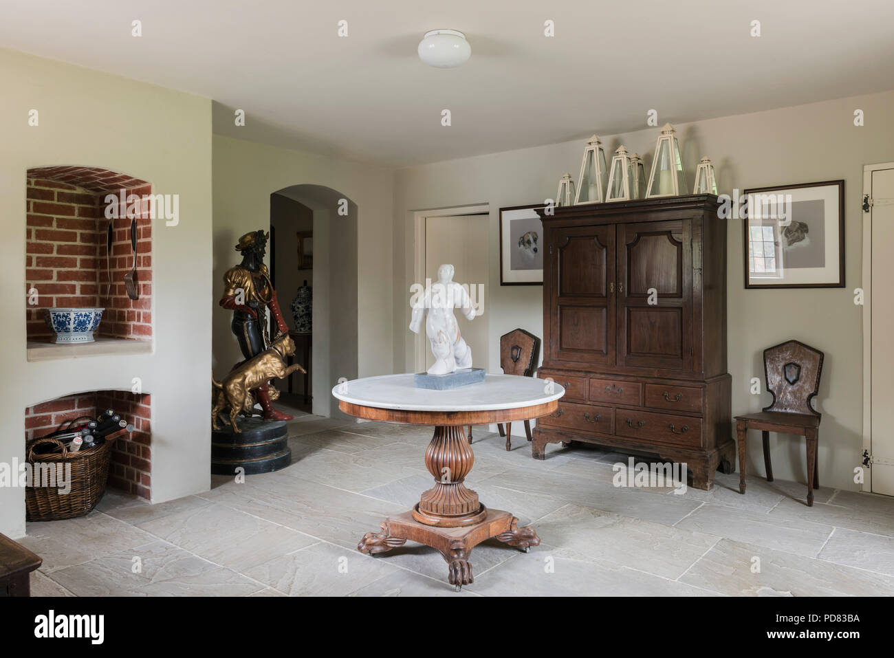 Claw footed table with marble top in entrance hall with flagstone flooring Stock Photo