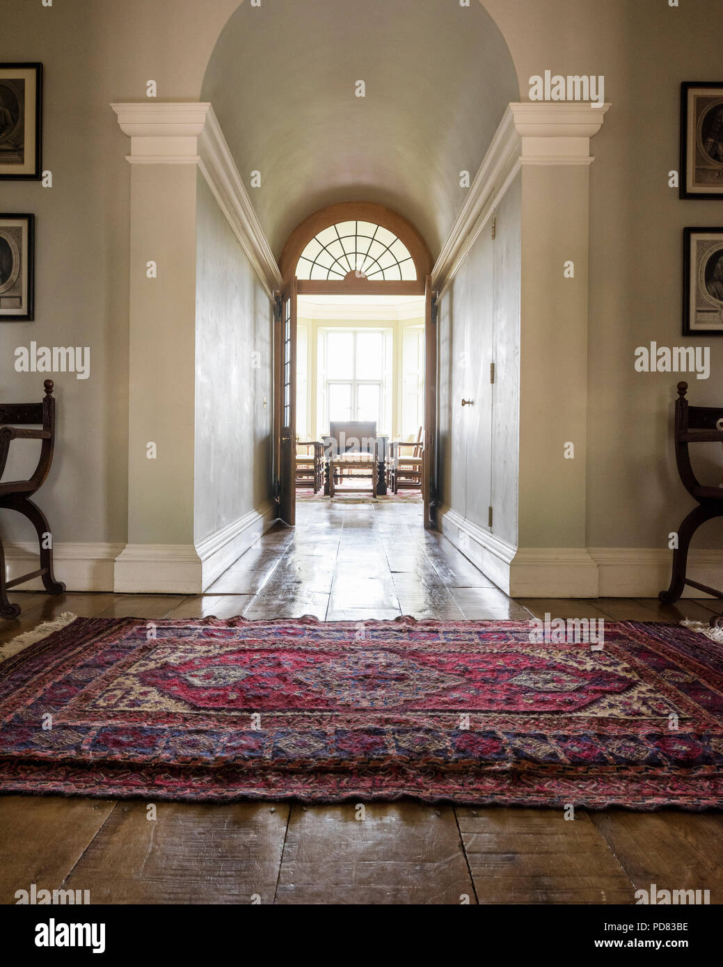 Antique rug in hall leading through to dining room with double doors Stock Photo