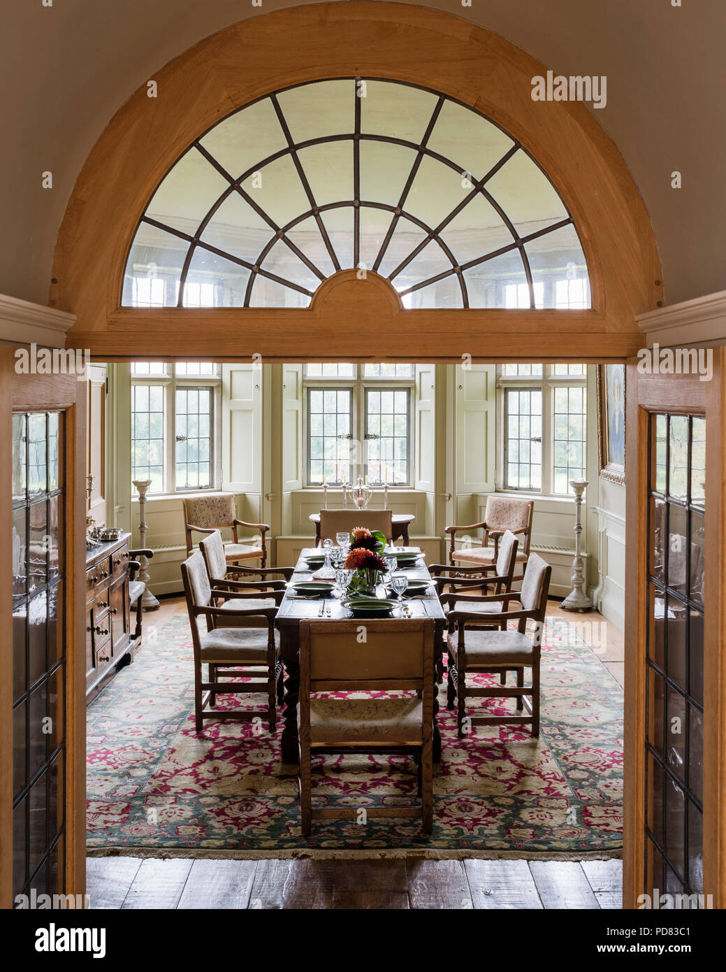 Glazed double doors lead into the dining room with 18th century dining chairs and oak sideboard Stock Photo