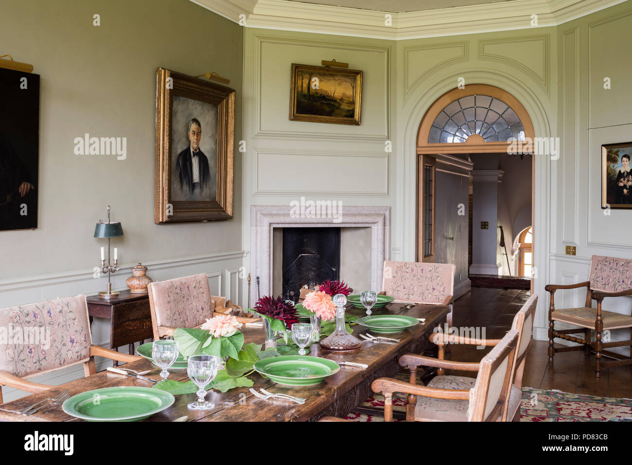 18th century dining chairs at table laid with green porcelain crystal glassware Stock Photo