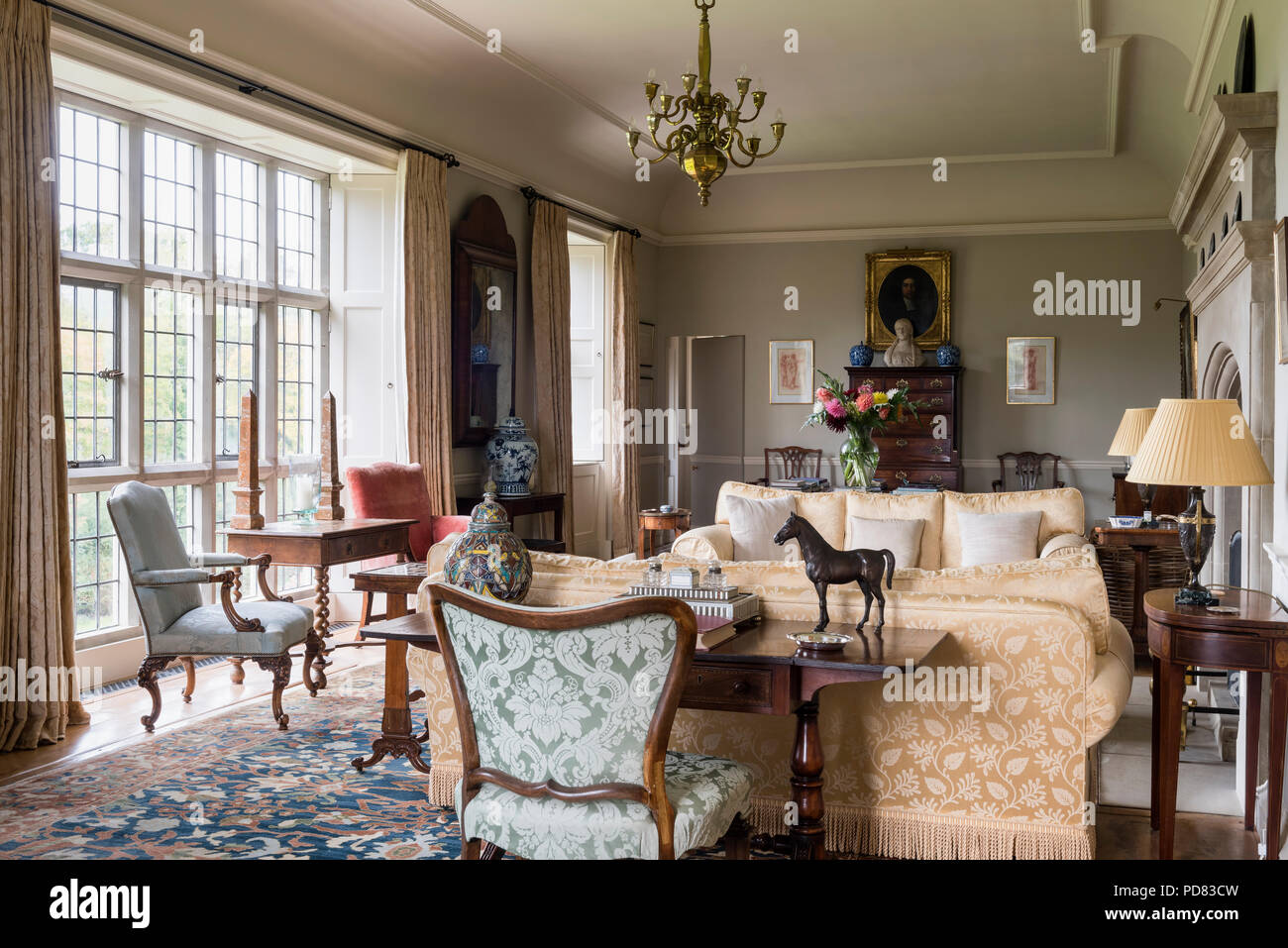 A 17th century table in the window of a large drawing room. The tall drawers at the back of the room are 18th century Stock Photo
