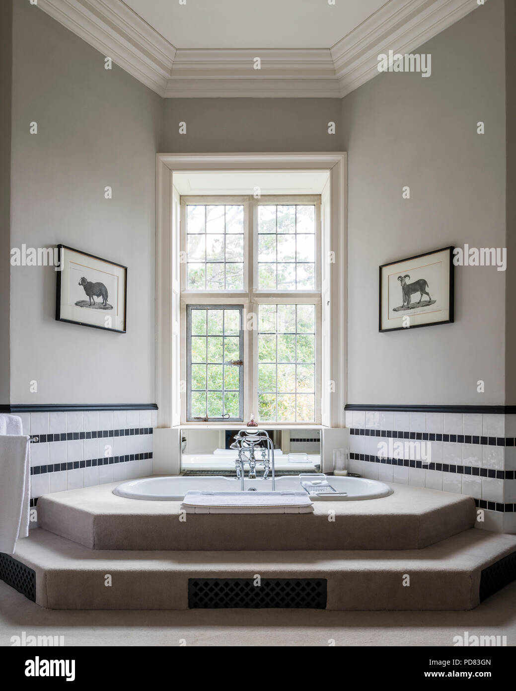 Luxury master bathroom with step up tub and black and white wall tiling Stock Photo