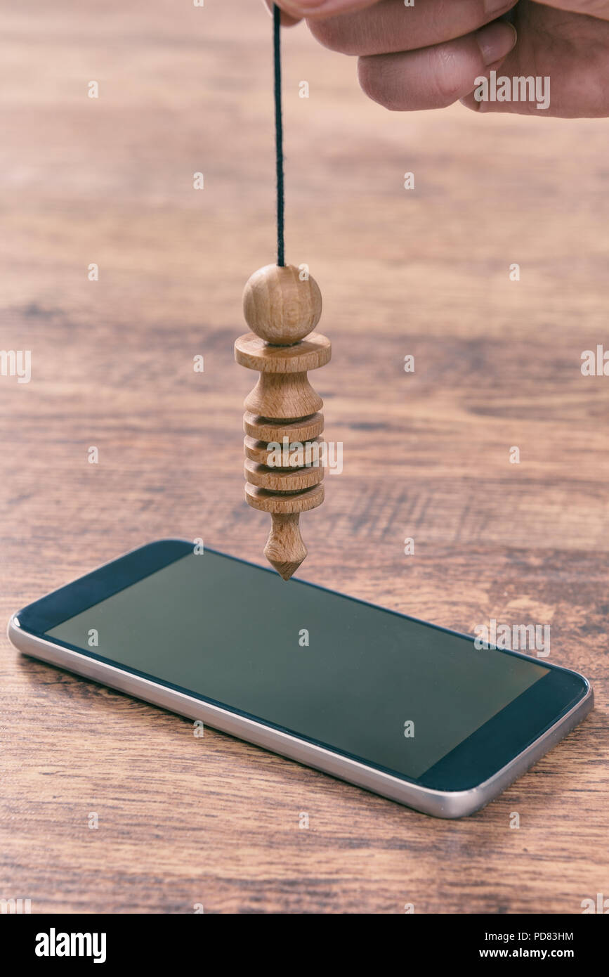 Hand with pendulum dowsing over smart phone to check its quality, dangerous influence or radiation - Stock Image