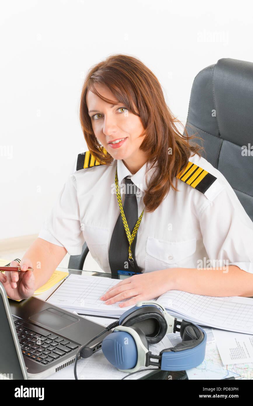 Beautiful woman pilot wearing uniform with epaulettes doing preflight briefing - Stock Image