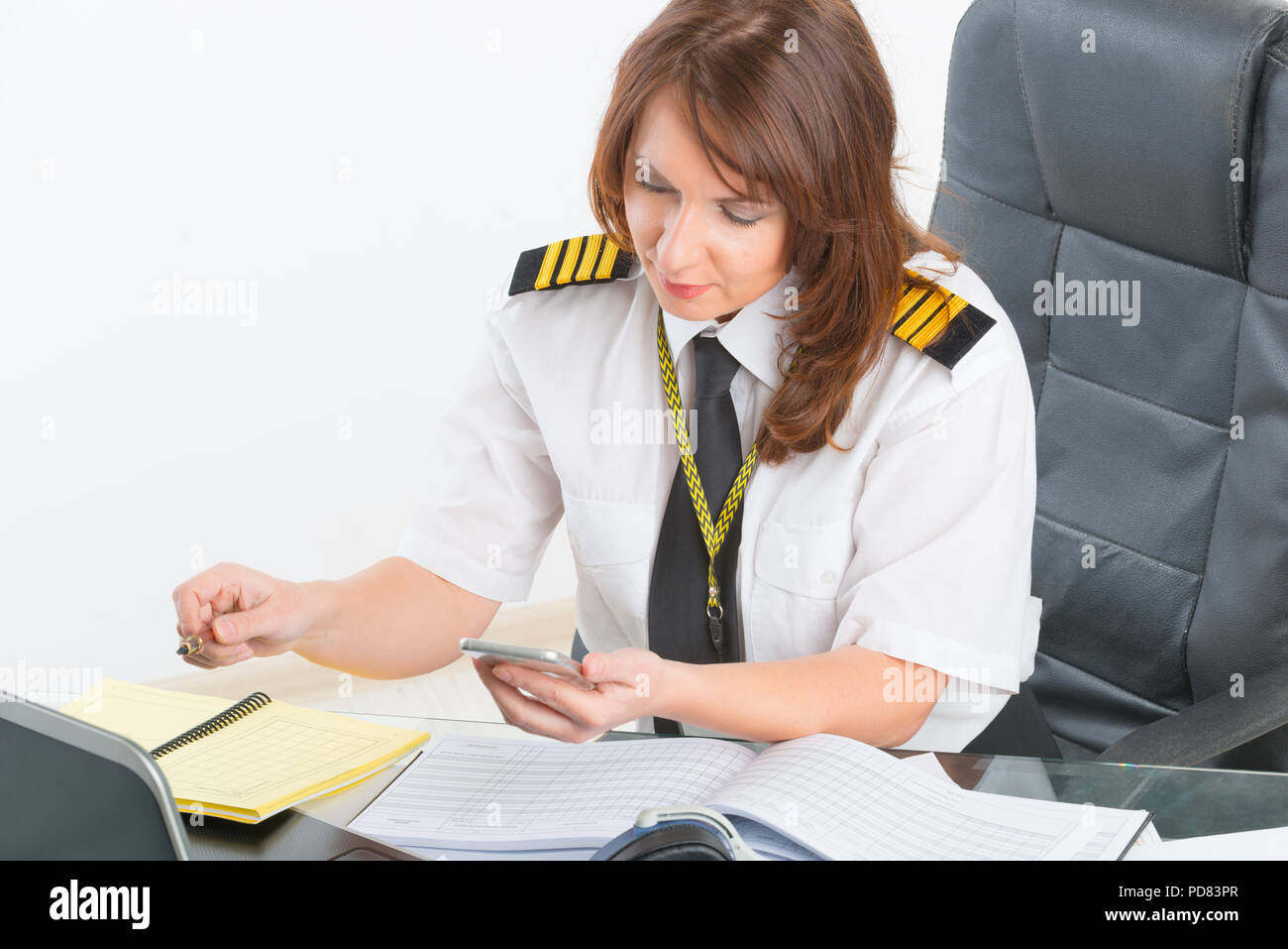 Beautiful woman pilot wearing uniform with epaulettes using mobile phone and laptop at preflight briefing - Stock Image