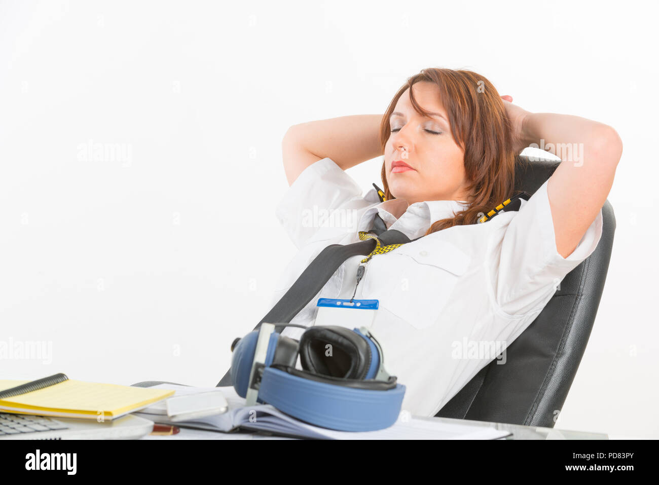 Overworked woman pilot wearing uniform with epaulettes resting or sleeping in briefing room - Stock Image