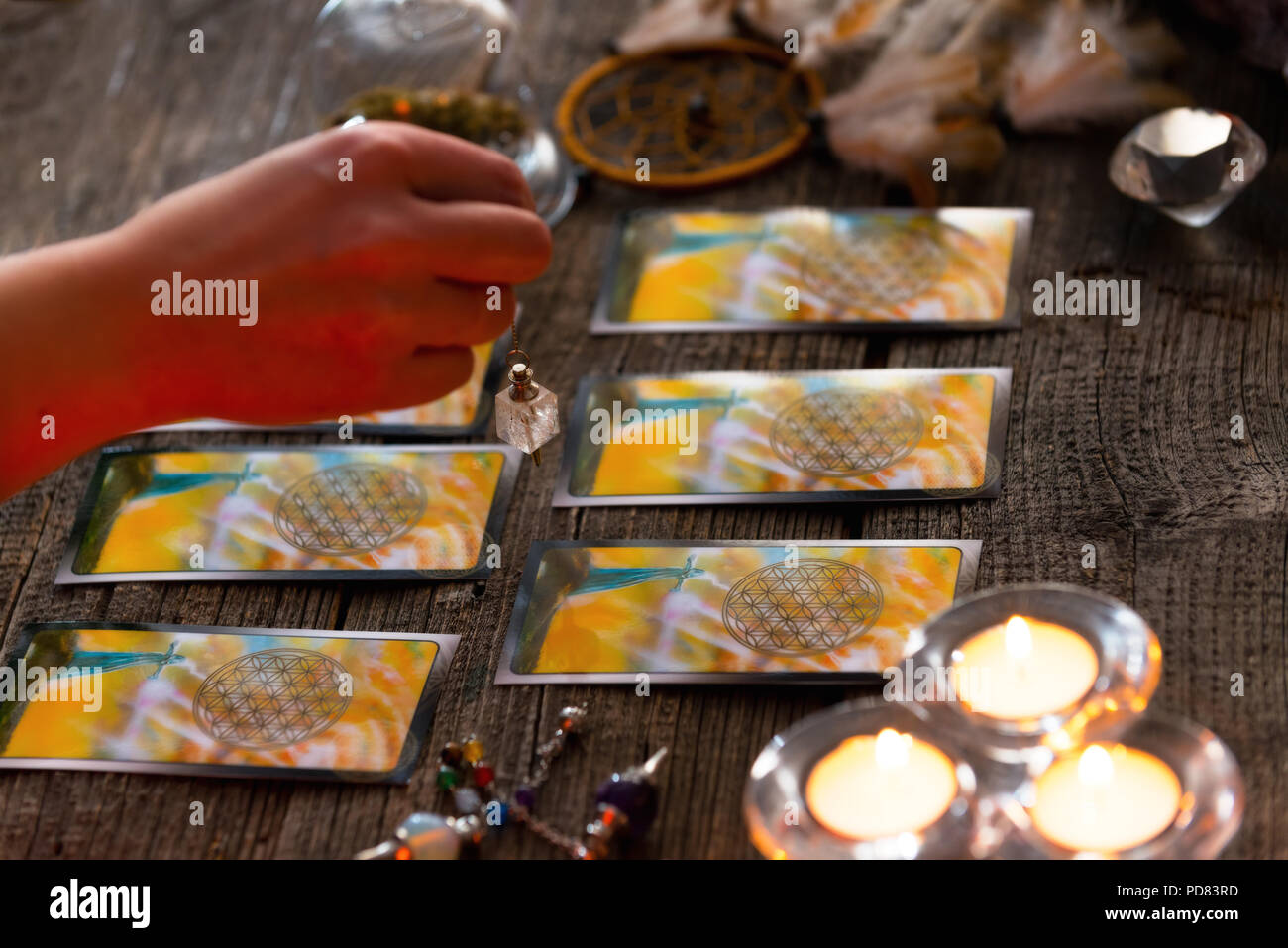 Fortune teller holding a pendulum over tarot cards Stock Photo