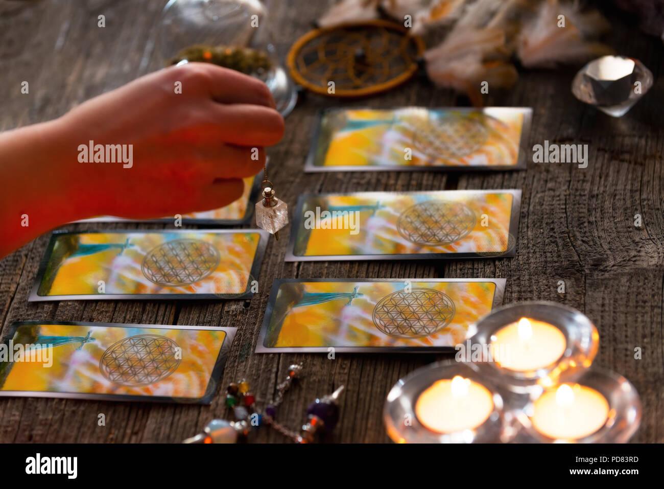 Fortune teller holding a pendulum over tarot cards - Stock Image