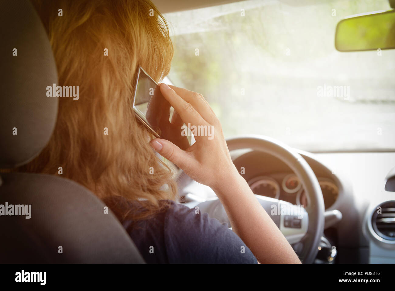 Woman using phone while driving the car. Risky driving behaviors concept - Stock Image