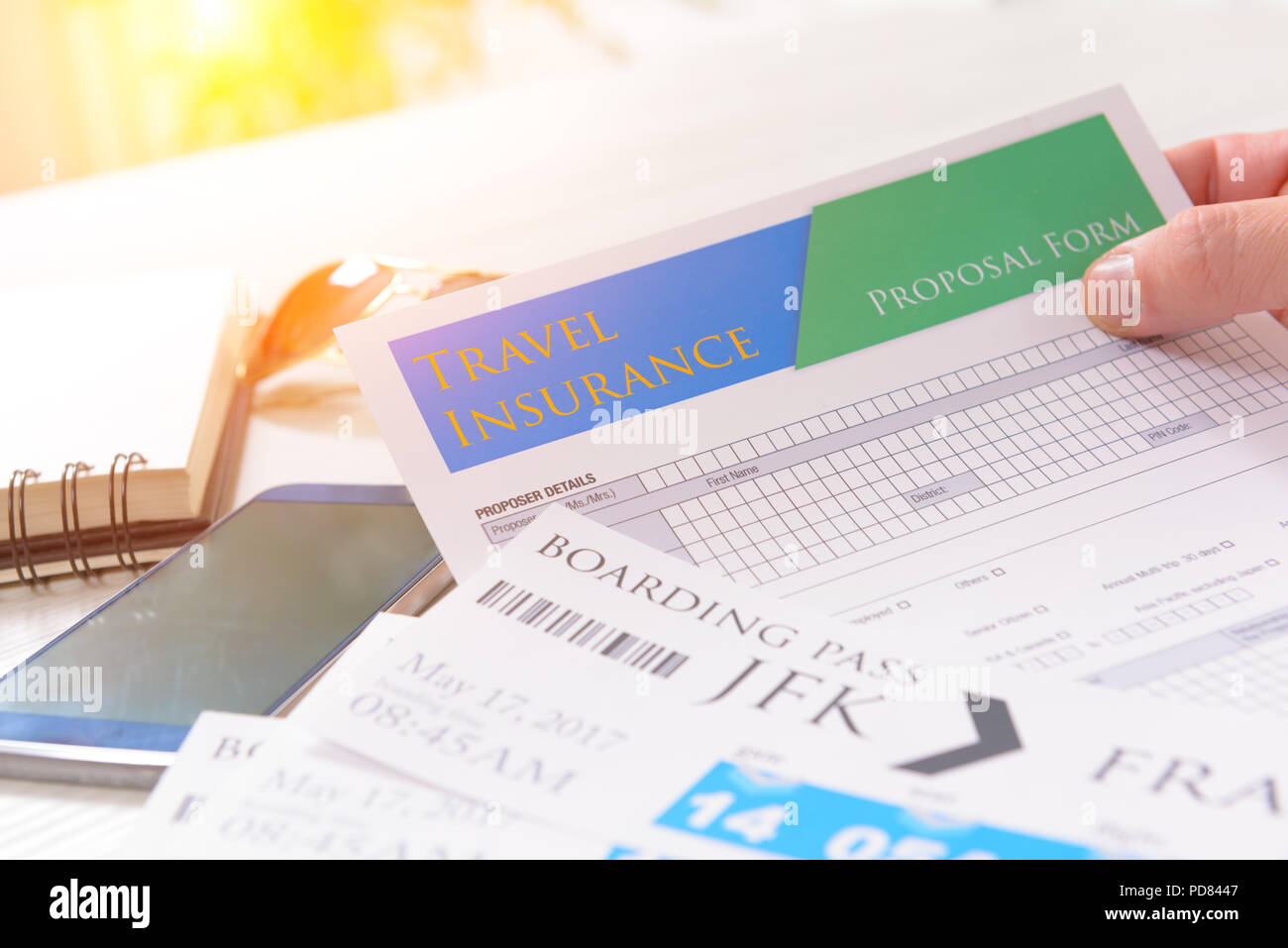 Airline boarding pass tickets in hand with travel insurance, sunglasses, pen and notebook as a concept of traveling - Stock Image