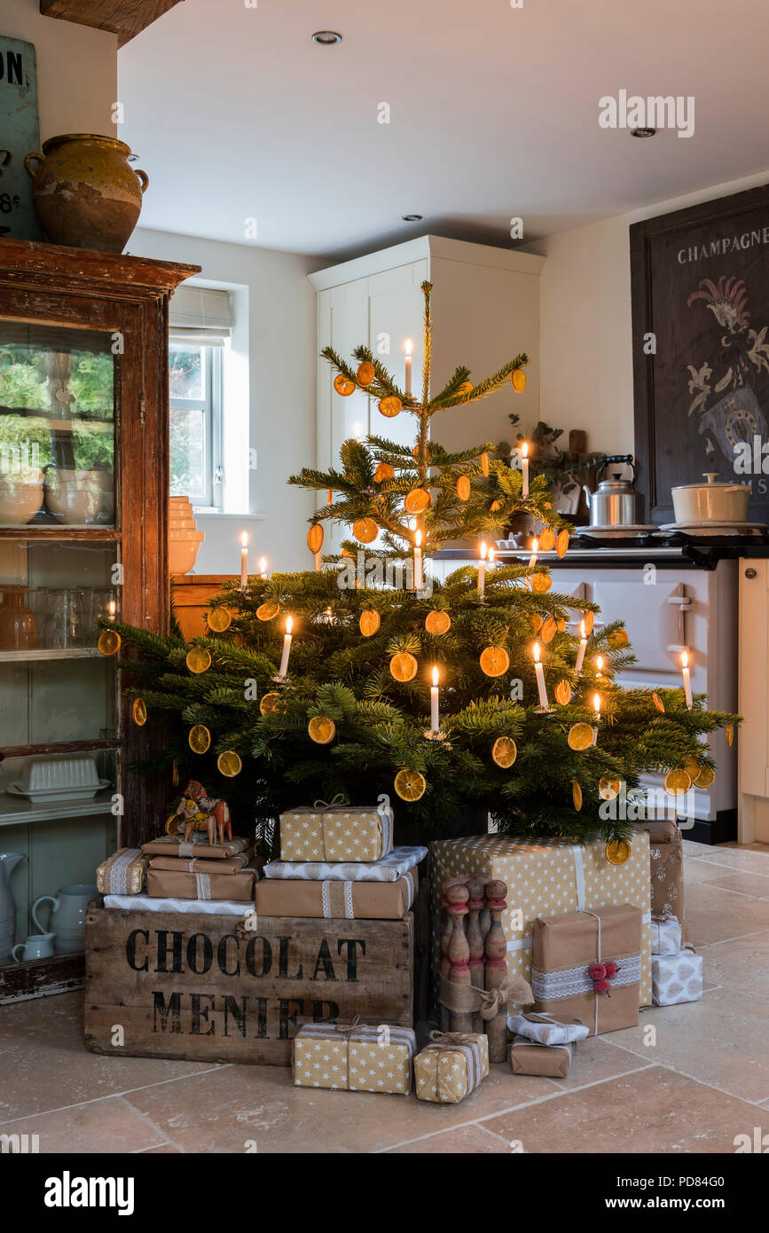 Candle lit christmas tree in cottage kitchen with wrapped presents ...