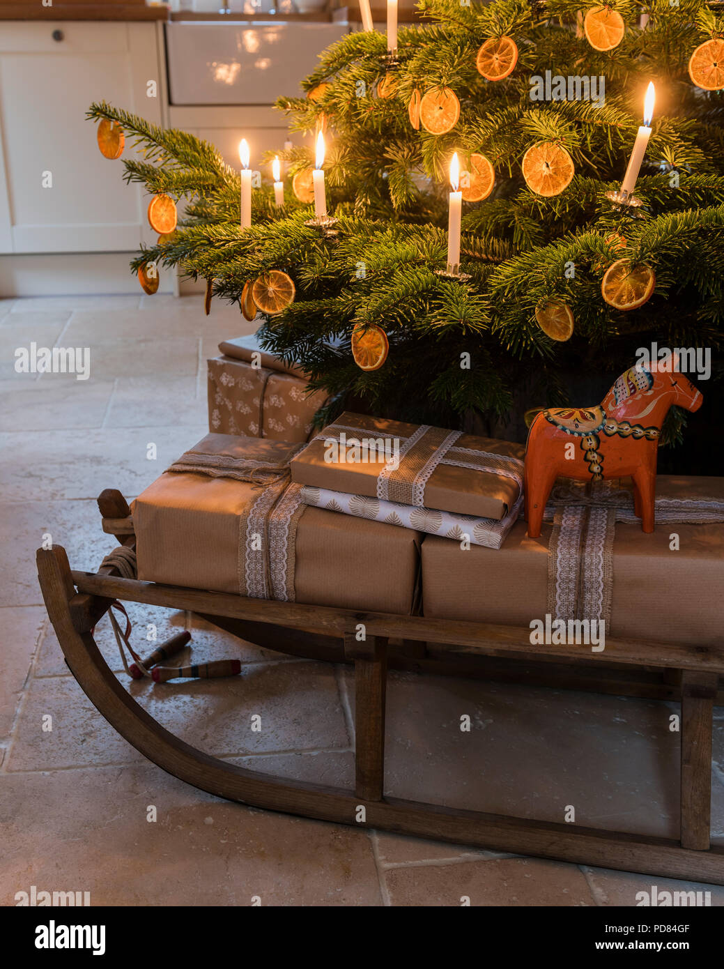 Wrapped presents on a wooden sledge underneath candle lit christmas tree - Stock Image
