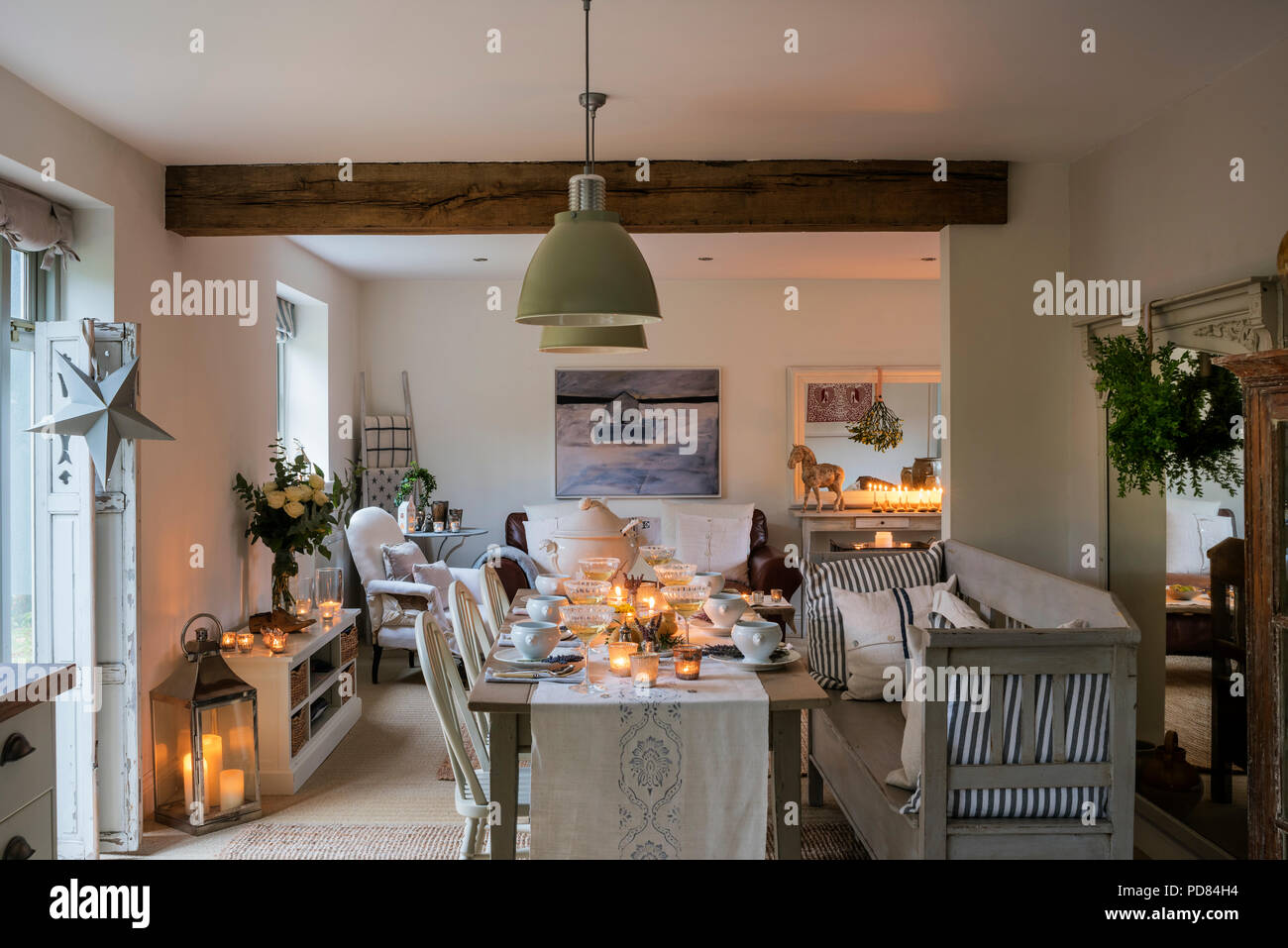 Candle lit dining table in rustic cottage kitchen with ...