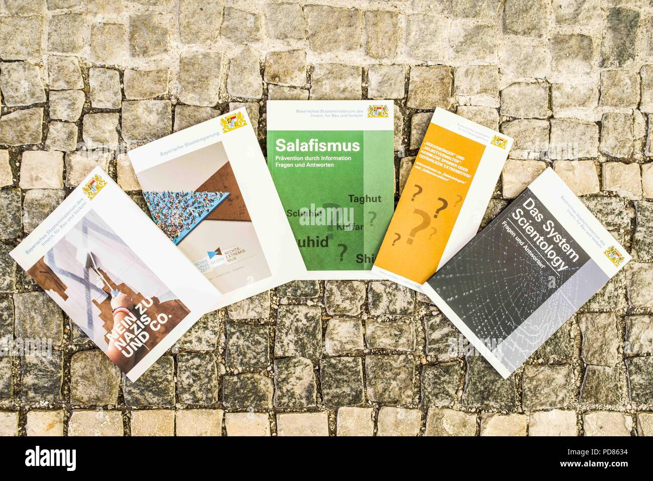 Munich, Bavaria, Germany. 7th Aug, 2018. Pamphlets with some of the challenges the Verfassungsschutz faces in maintaining law and order in Bavaria and Germany. JOACHIM HERRMANN, the Interior Minister of Bavaria, presented the half-year report of the Verfassungschutz (Geheimdienst, Secret Service). Herrmann stated that the challenges for the Verfassungsschutz are becoming more complex and multi-faceted, including right and left extremism, as well as islamists, islamophobes, foreigner criminality, Reichsbuerger (sovereign citizens), and Scientology. The Verfassungsschutz is a secret service - Stock Image