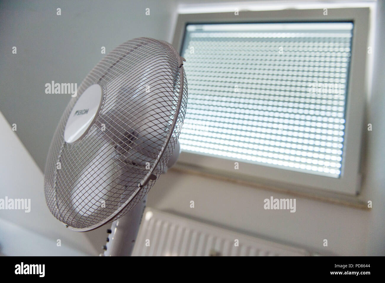 Munich, Germany. 06th Aug, 2018. 06.08.2018, Munich: A fan rotates in front of a tilted window in front of which the roller shutters have been lowered. The persistent heat makes it difficult to stay in the apartment during the day. Credit: Lino Mirgeler/dpa/Alamy Live News - Stock Image
