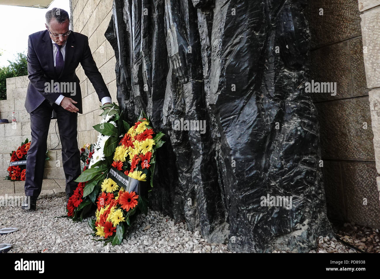 Jerusalem, Israel. 7th August, 2018. Polish Ambassador to Israel, MAREK MAGIEROWSKI, places a flower wreath at the foot of 'Korczak And The Ghetto's Children' by Boris Saktsier in a memorial ceremony marking 76 years since the death of Janusz Korczak. Korczak, born Henryk Goldszmit in 1878, a Polish Jewish educator and pediatrician, director of an orphanage in Warsaw, refused personal freedom and escorted his 200 orphans, forced to the Treblinka death camp, where they were all exterminated in 1942. Credit: Nir Alon/Alamy Live News Stock Photo