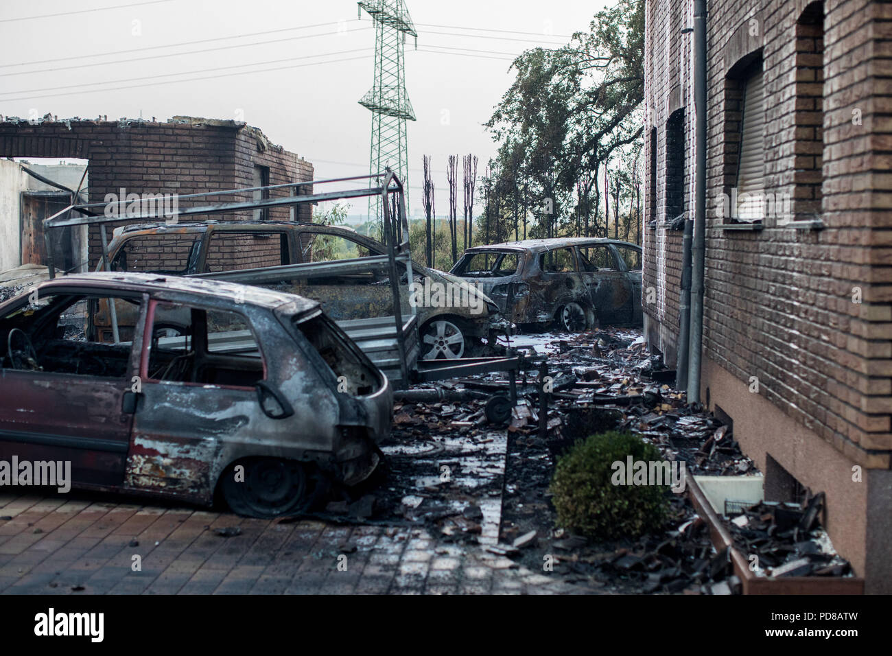 Siegburg, Germany. 07th Aug, 2018. completely burnt cars stand in front of an apartment building. Several houses caught fire due to a fire directly on the important Cologne-Frankfurt railway line. Credit: Marcel Kusch/dpa/Alamy Live News - Stock Image