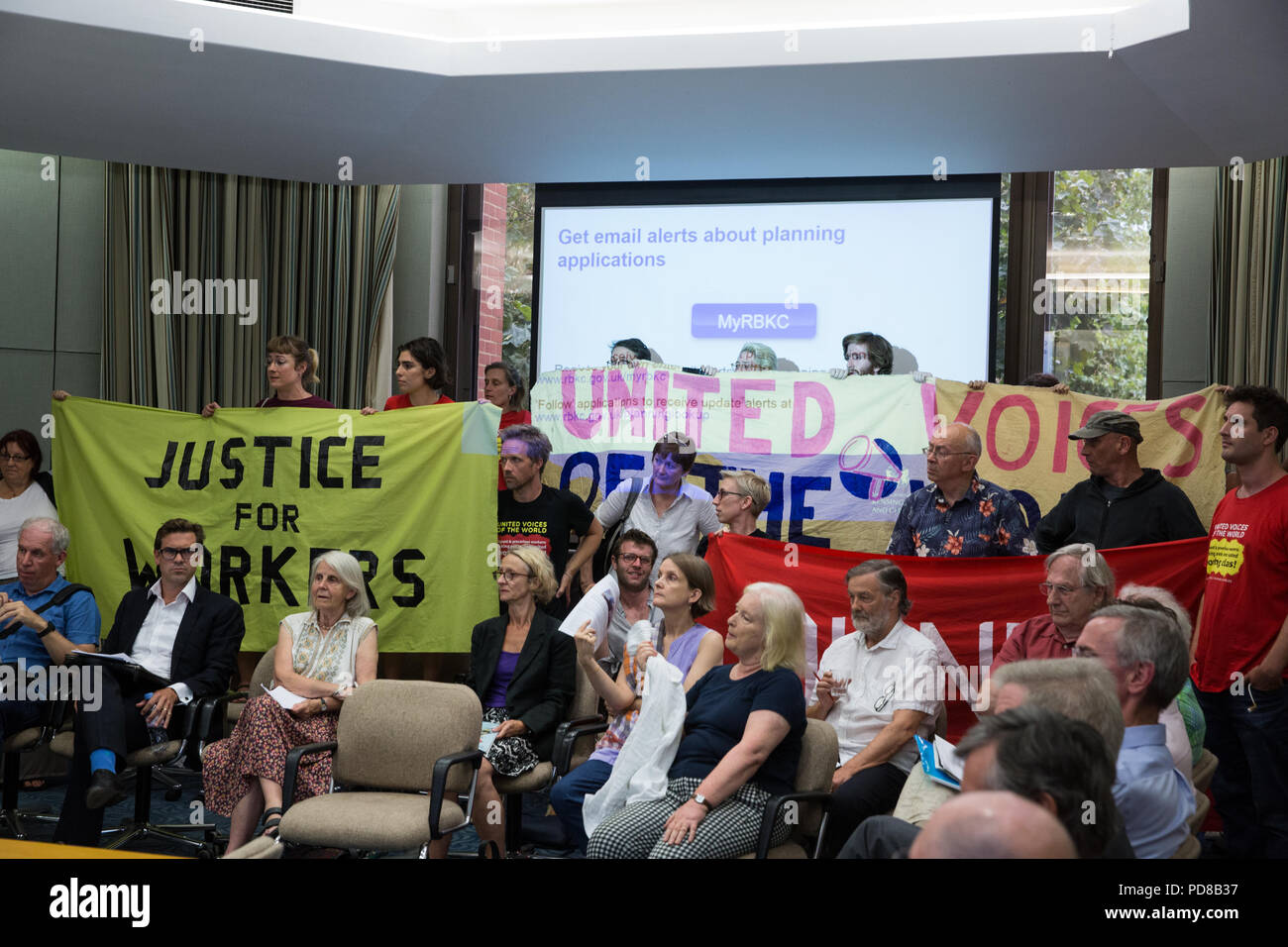 London, UK. 7th August, 2018. Members and supporters of the United Voices of the World (UVW) trade union protest inside a Planning Committee meeting to draw attention to a strike by migrants working for the Royal Borough of Kensington and Chelsea. Striking workers are seeking an occupational sick pay scheme, parity of terms and conditions with directly employed staff and payment of the London Living Wage with guaranteed annual increments. Credit: Mark Kerrison/Alamy Live News - Stock Image