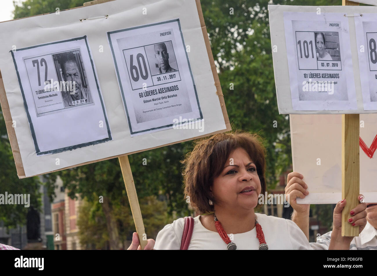 London, UK. 7th August 2018. A Colombian woman holds placards with pictures of some of the over a hundred murdered community leaders at a  protest in Parliament Square in support of the peace process in Colombia and demanding an end to the daily threats and murders throughout the country. ook place today at the UN in New York, the Inte Credit: Peter Marshall/Alamy Live News Stock Photo