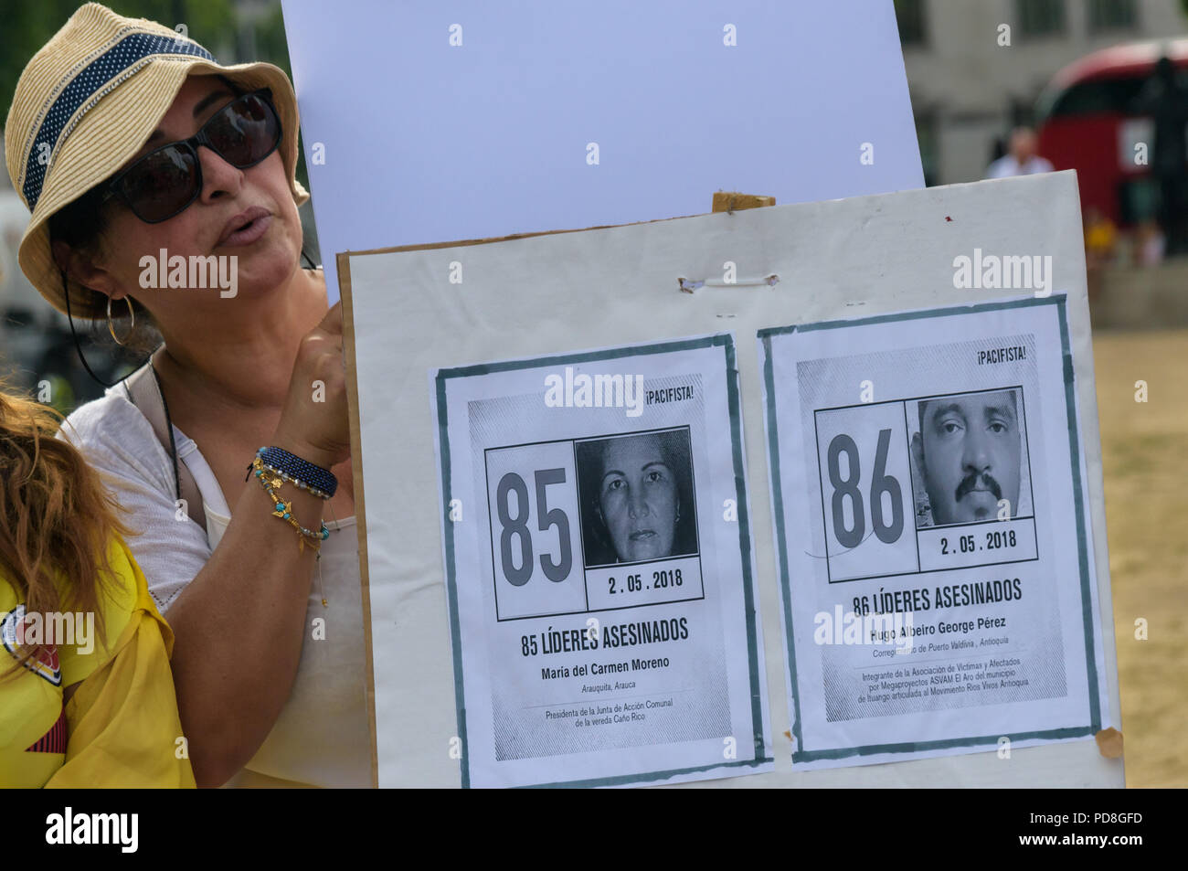 London, UK. 7th August 2018. A Colombian holds placards with pictures of some of the over a hundred murdered community leaders at a  protest in Parliament Square in support of the peace process in Colombia and demanding an end to the daily threats and murders throughout the country. ook place today at the UN in New York, the Internatio Credit: Peter Marshall/Alamy Live News Stock Photo