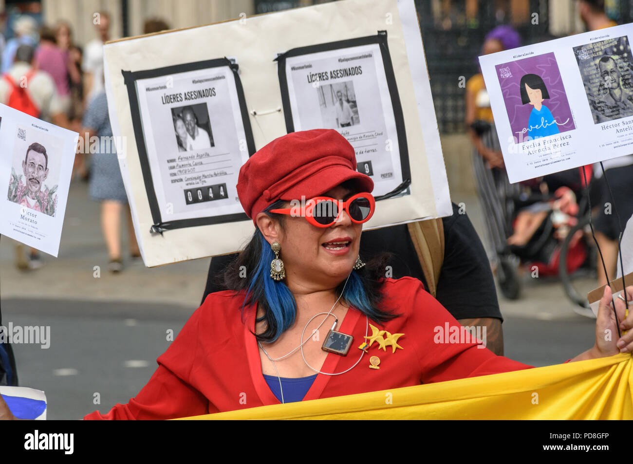 London, UK. 7th August 2018. A Colombian woman holds the flag and placards with pictures of some of the over a hundred murdered community leaders at a  protest in Parliament Square in support of the peace process in Colombia and demanding an end to the daily threats and murders throughout the country. ook place today at the UN in New Y Credit: Peter Marshall/Alamy Live News Stock Photo