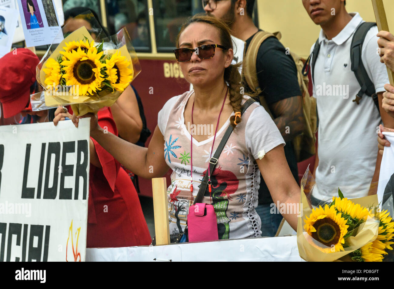 London, UK. 7th August 2018. A Colombian woman holds bunches of sunflowers at a  protest in Parliament Square in support of the peace process in Colombia and demanding an end to the daily threats and murders throughout the country. ook place today at the UN in New York, the International Court of Justice in The Hague, and in Washington Credit: Peter Marshall/Alamy Live NewsStock Photo