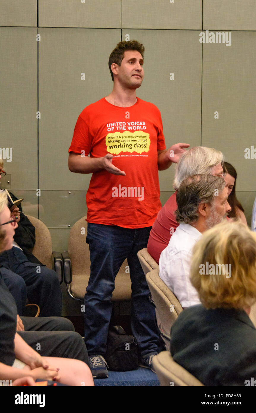London, UK. 7th August 2018. Petros Elia of United Voices of the World trade union stands up in a  Kensington & Chelsea council planning committee public meeting to state the case for the cleaners to receive the London Living Wage.  The union were angered by the withdrawal of a promise made earlier in the day to bring the cleaners at the council back into direct employment. The meeting was suspended after his statement, with most councillors leaving and there was a short debate where a councillor and several members of the public spoke supporting the cleaners; the protesters left after CouncilStock Photo