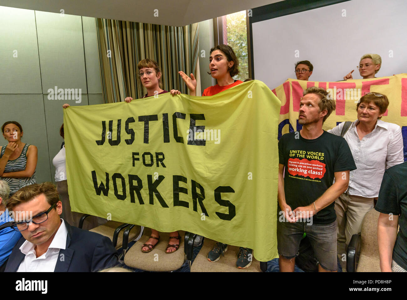 London, UK. 7th August 2018.  United Voices of the World trade union members speak in the debate after the  Kensington & Chelsea council planning committee public meeting was officially suspended.  The union were angered by the withdrawal of a promise made earlier in the day to bring the cleaners at the council back into direct employment. The meeting was suspended after his statement, with most councillors leaving and there was a short debate where a councillor and several members of the public spoke supporting the cleaners; the protesters left after Councillor Catherine Faulks gave a promise Stock Photo