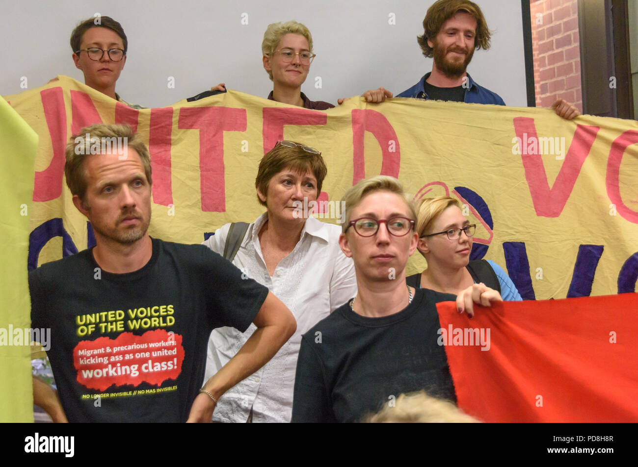 London, UK. 7th August 2018.  United Voices of the World trade union members hold banners and listen to the debate after the  Kensington & Chelsea council planning committee public meeting was officially suspended.  The union were angered by the withdrawal of a promise made earlier in the day to bring the cleaners at the council back into direct employment. The meeting was suspended after his statement, with most councillors leaving and there was a short debate where a councillor and several members of the public spoke supporting the cleaners; the protesters left after Councillor Catherine FauStock Photo