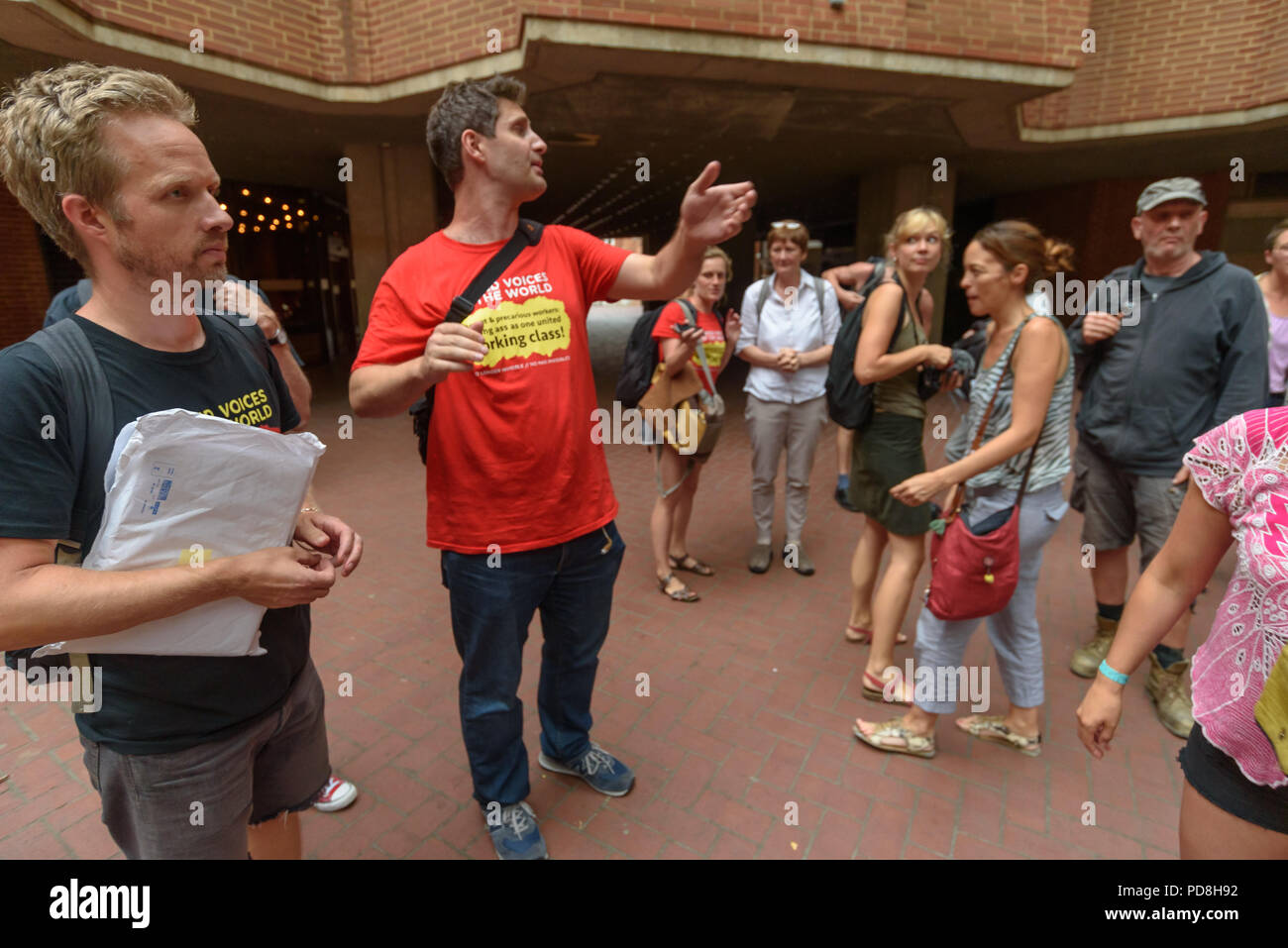 London, UK. 7th August 2018. Petros Elia of the United Voices of the World trade union tells the cleaners who had been waiting outside the council offices what had happened at the protest inside the meeting. Angered by the withdrawal of a promise made earlier in the day to bring the cleaners at Kensington & Chelsea council back into direct employment the UVW had decided to interrupt a council planning committee public meeting to state the case for the cleaners to receive the London Living Wage. The meeting was suspended, with most councillors leaving and there was a short debate where a counci Stock Photo
