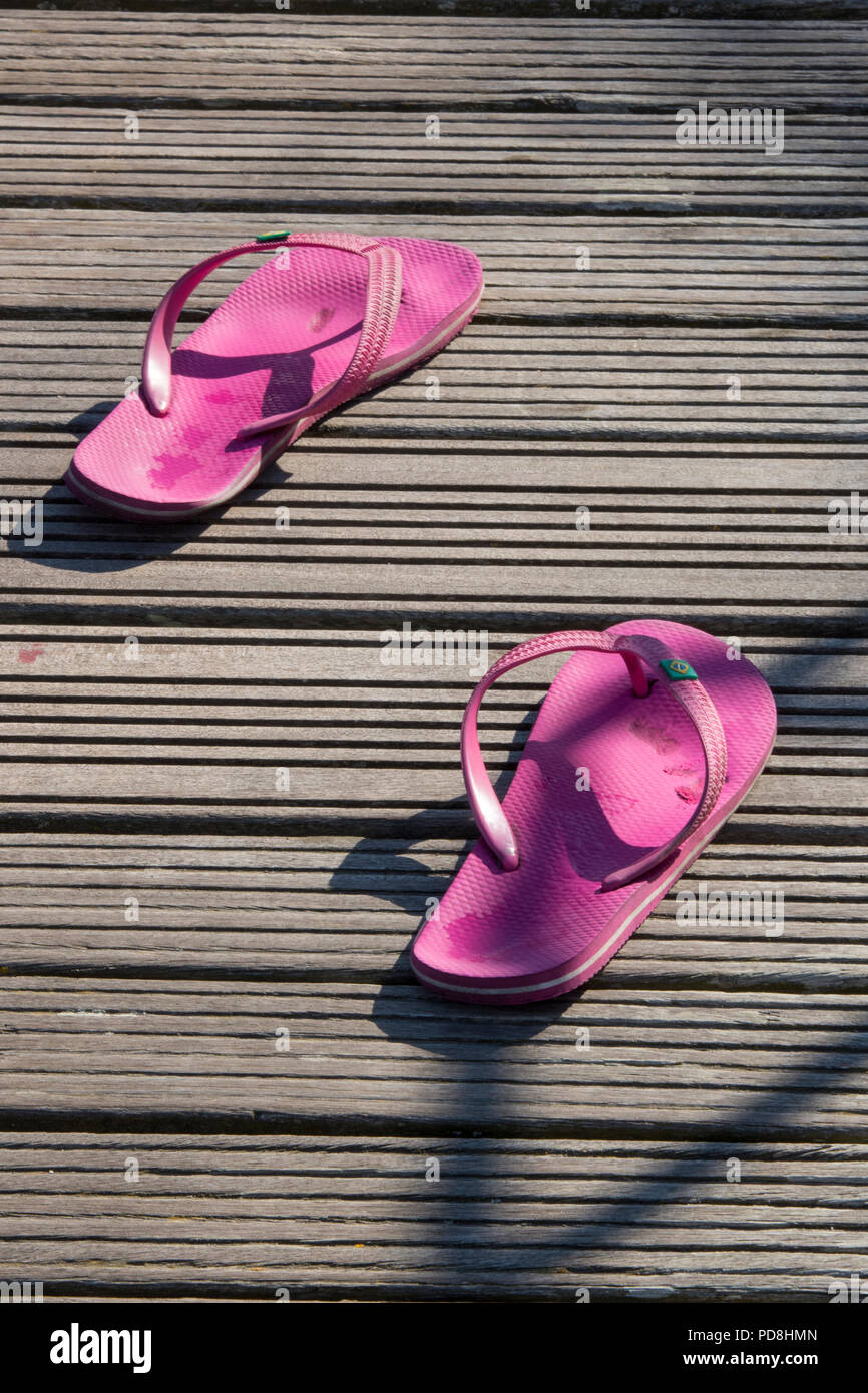 a pair of pink flip flops shoes on some wooden decking casting a shadow on the wood. - Stock Image