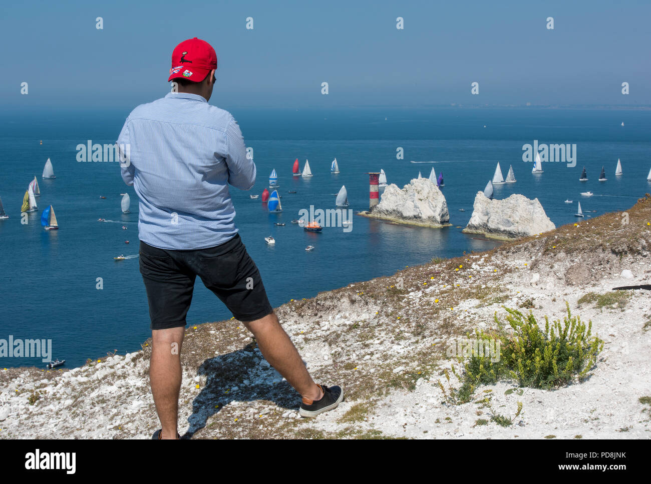 an atmospheric view of the round the island yacht race on the isle of wight with a man standing on the cliff edge watching at the needles lighthouse. - Stock Image