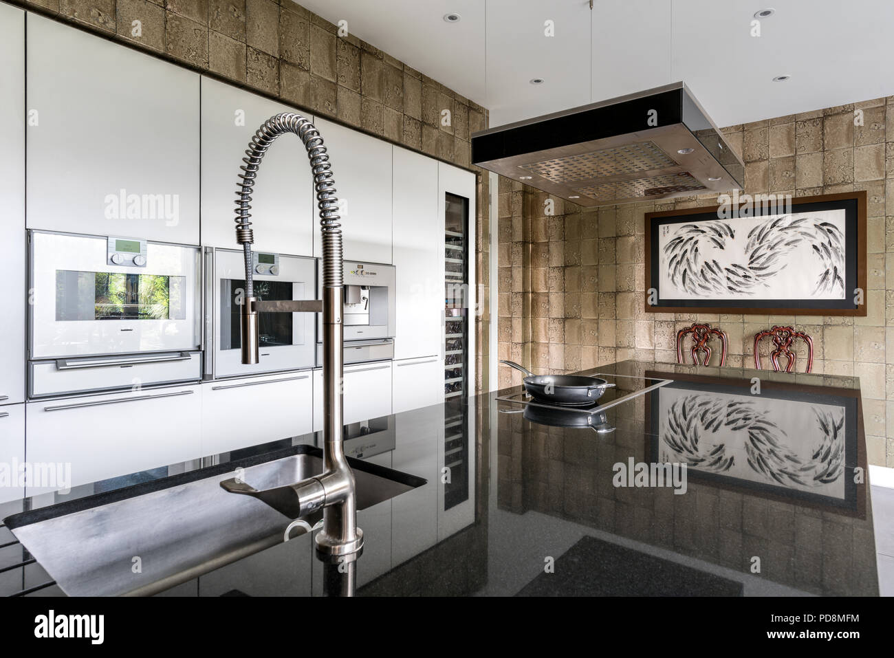 Frying pan on hob with hose tap in sleek London kitchen - Stock Image