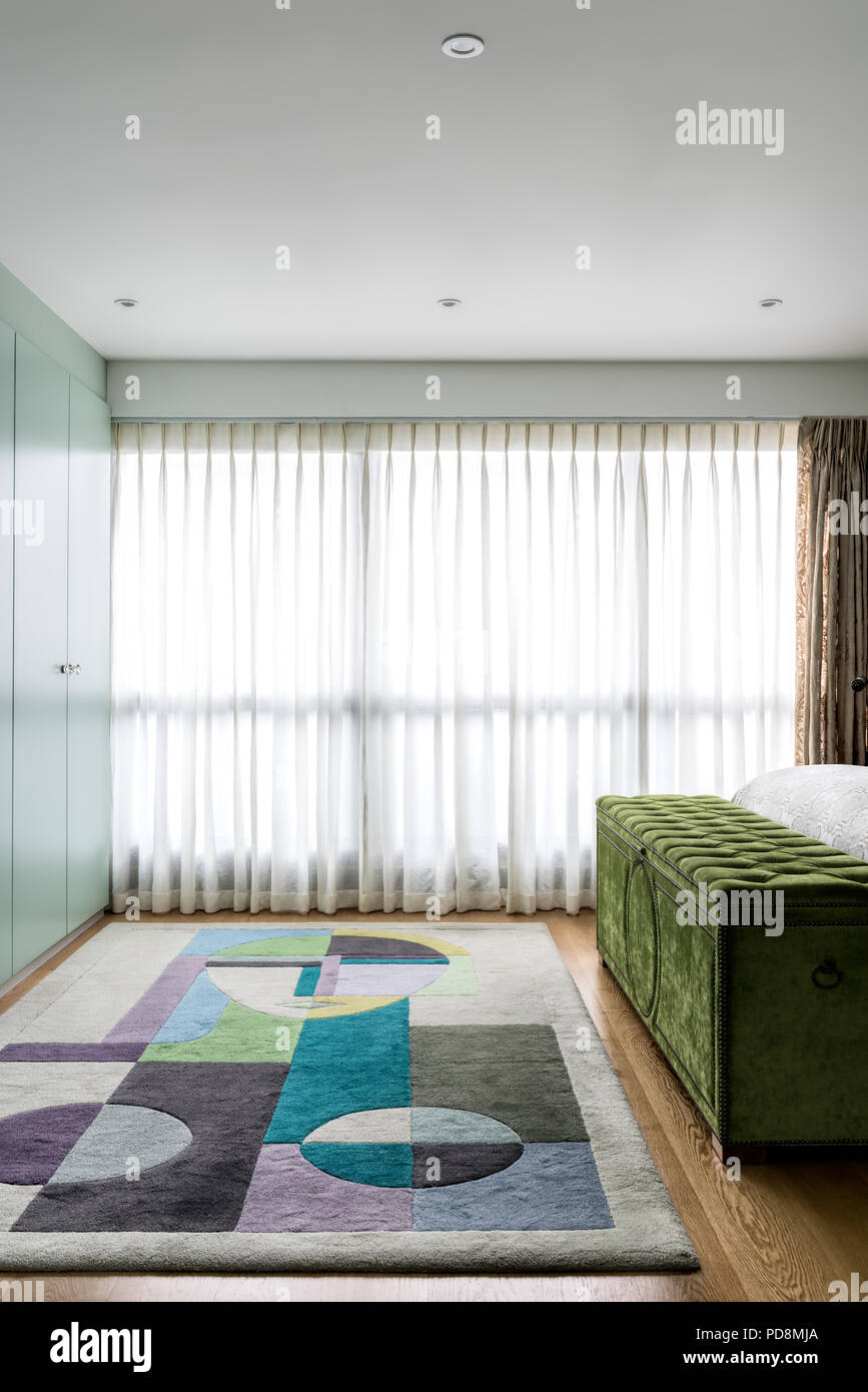Lime green velvet blanket box with colourful rug and closed blinds - Stock Image