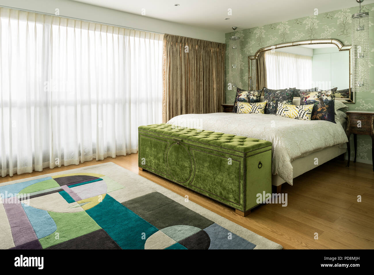 Lime green blanket box at foot of bed in room with net curtains - Stock Image