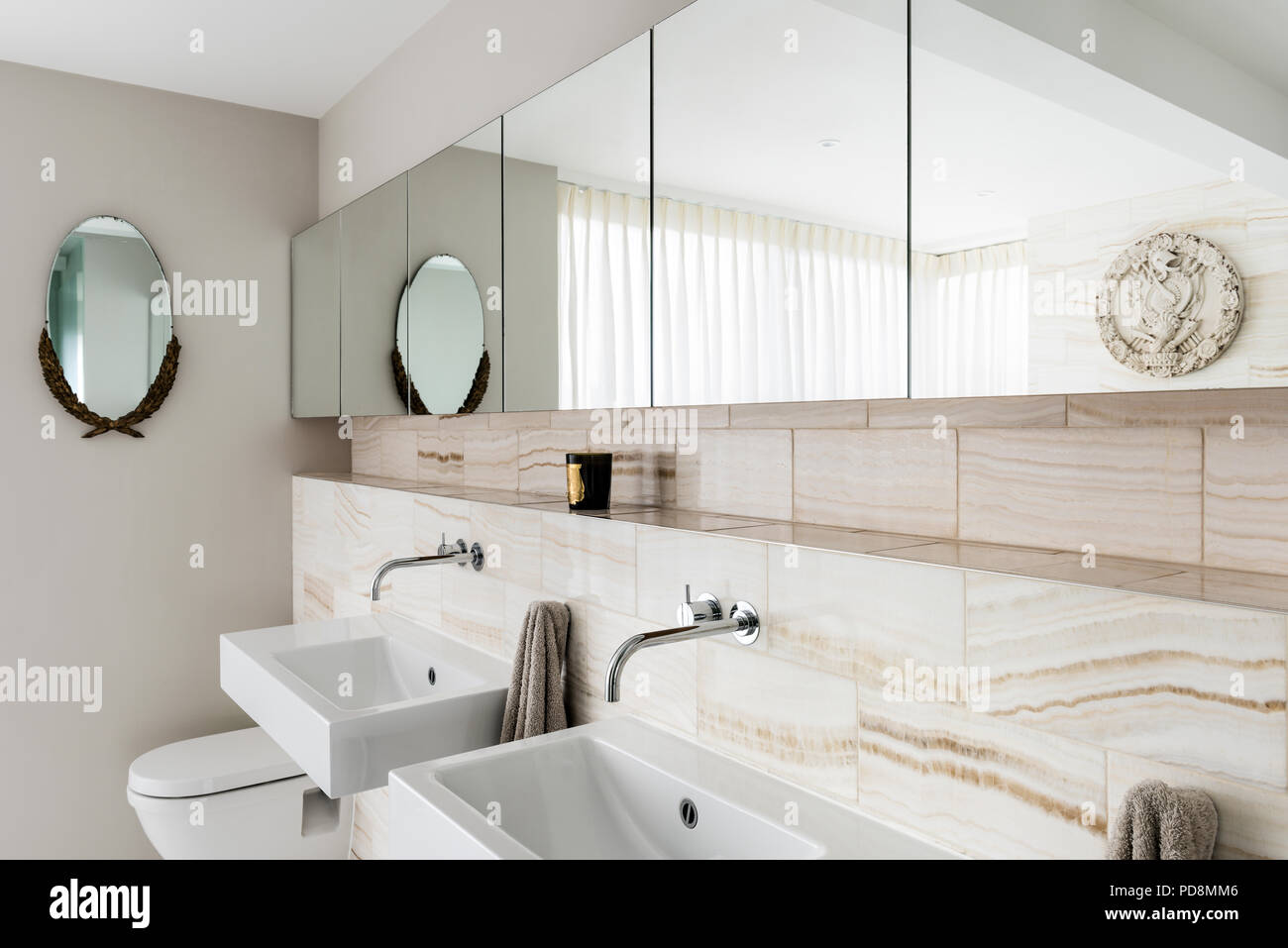 Mirrored cabinets above recessed marble shelf amd washbasins - Stock Image