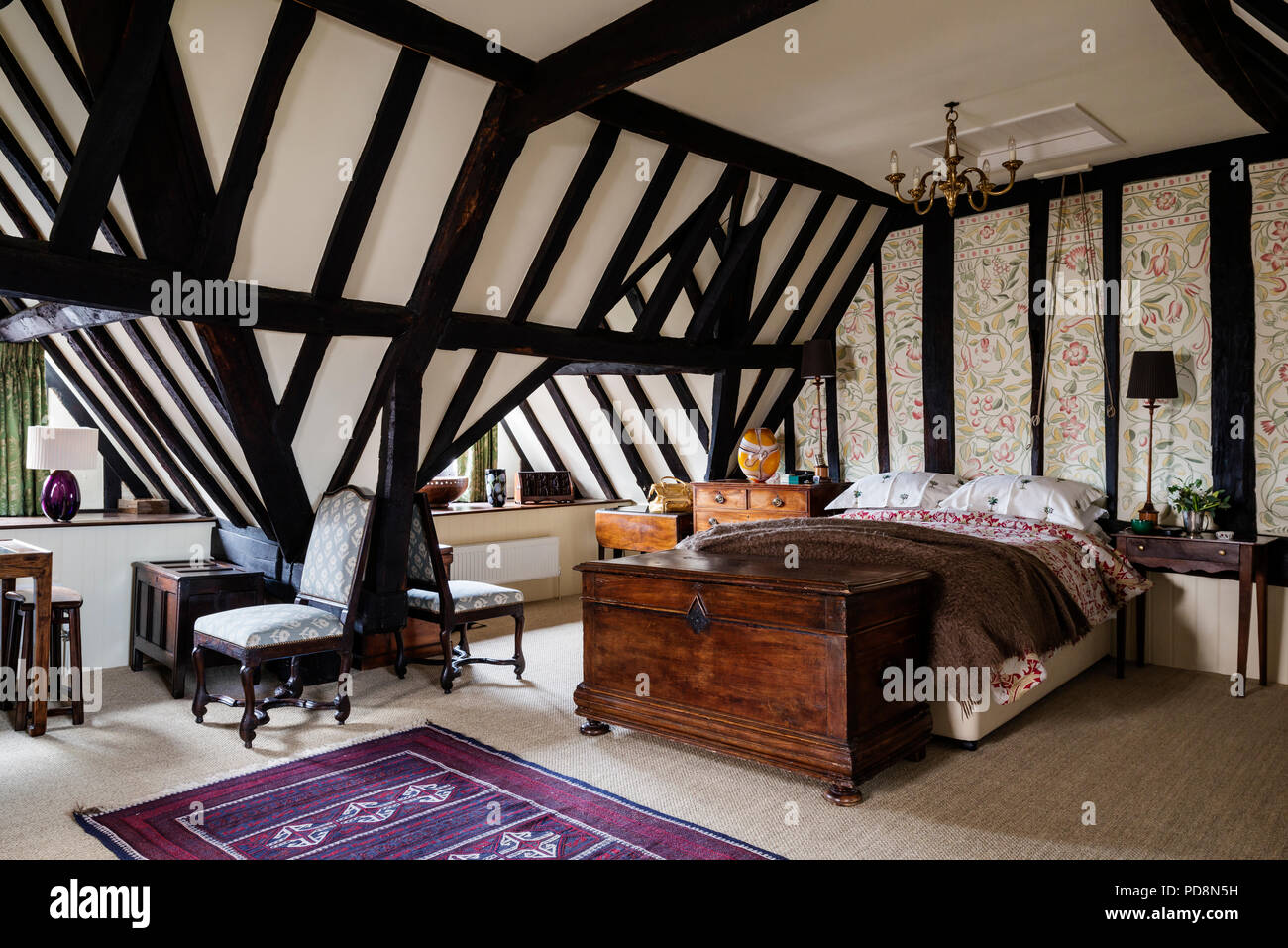 Timber framed bedroom with dormer windows and Tudor style floral motif - Stock Image