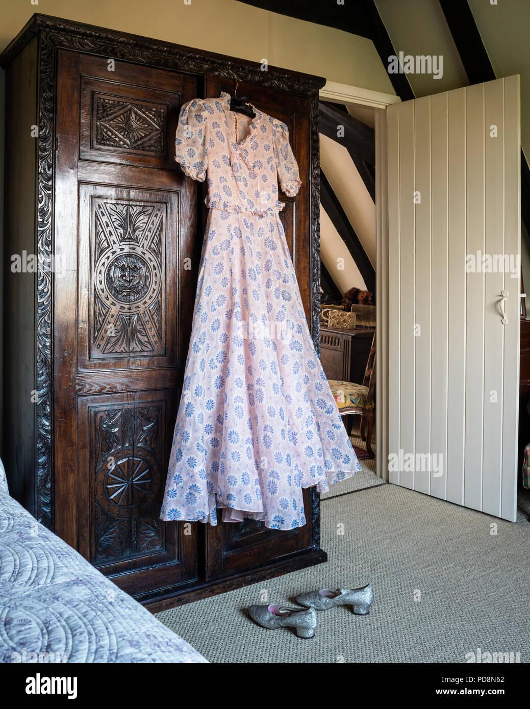 1930s vintage dress hanging on antique carved oak wardrobe - Stock Image