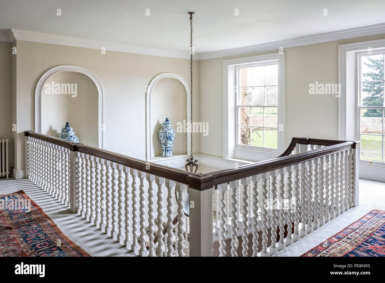 Wooden handrail in classic wide staircase - Stock Image