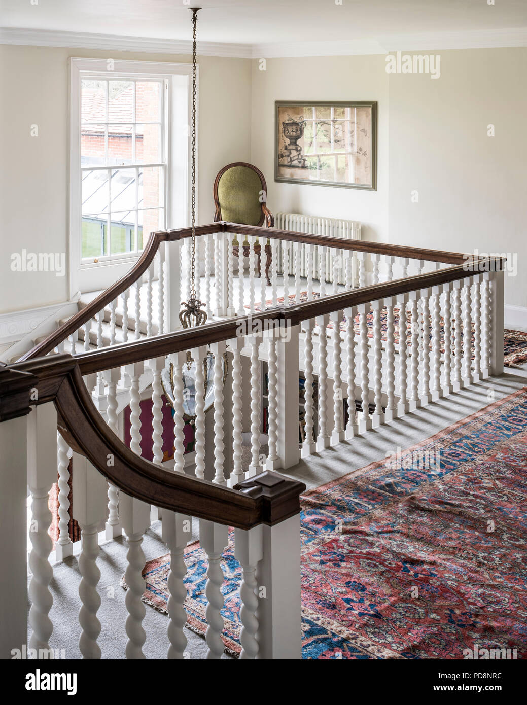 Wooden handrail and chair in wide staircase landing - Stock Image