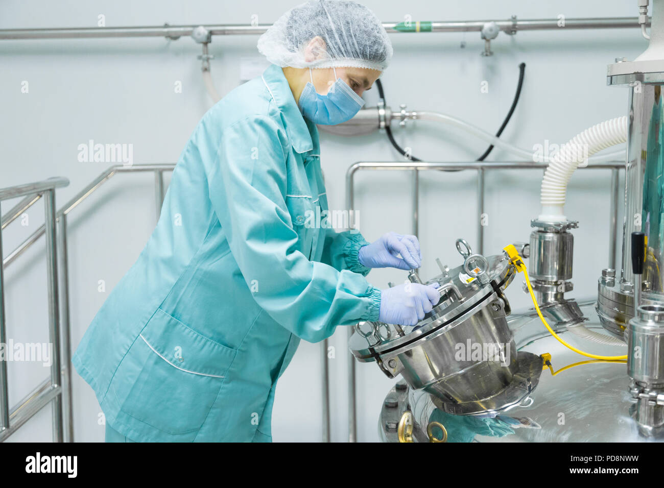 Pharmaceutical factory woman worker in protective clothing operating production line in sterile environment - Stock Image
