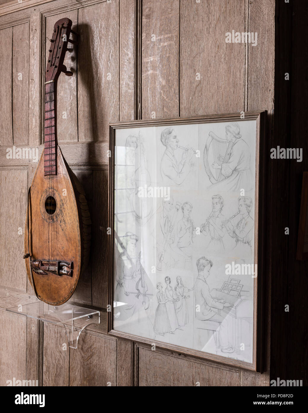 Stringed instrument and framed artwork of musicians playing instruments - Stock Image