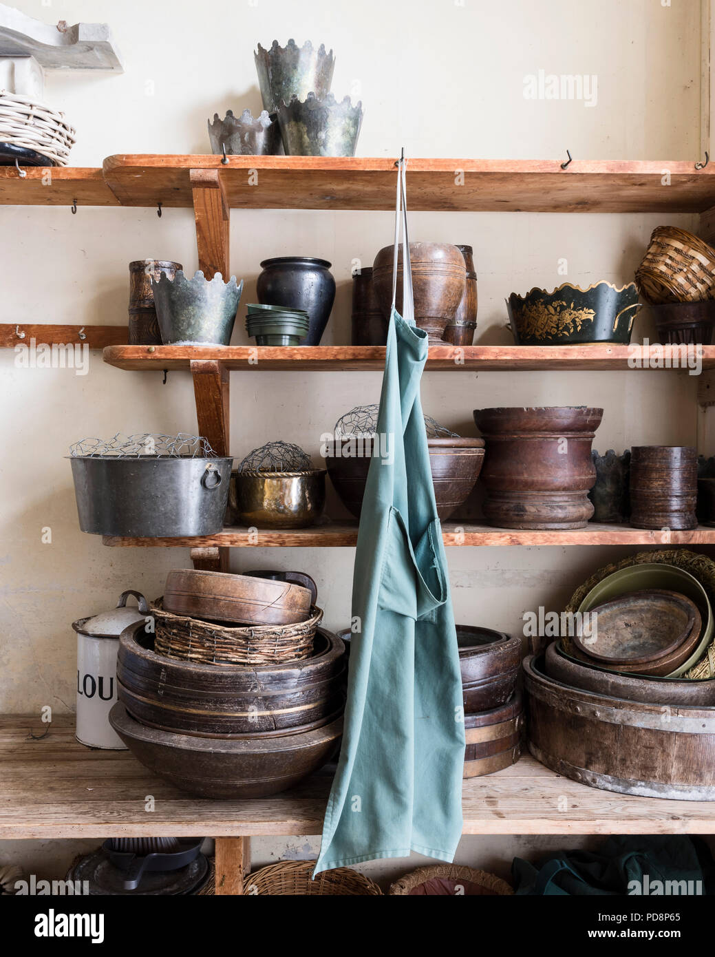 Collection of eathenware gardening pots on wooden shelves - Stock Image