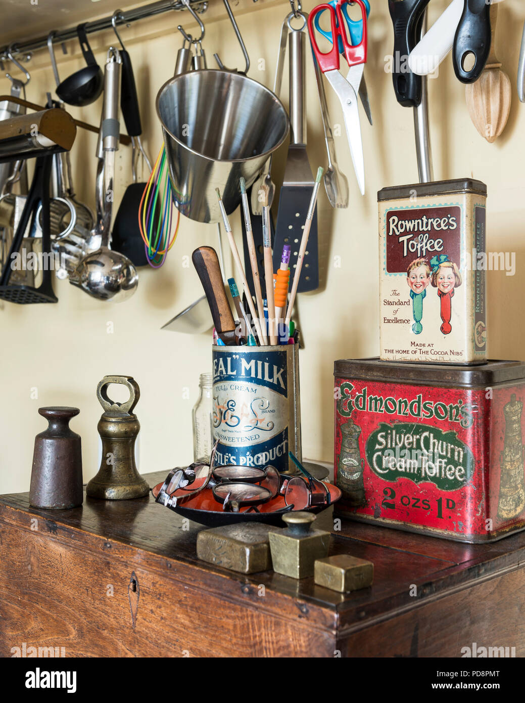 Brass weights and vintage sweet tins sit on an old oak box. Above various kitchen utensils hang from a wall rack - Stock Image