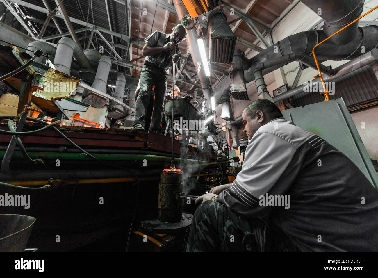 Minsk, Belarus - February 01, 2018: Glass factory workers on production of glass background working with manufacture equipment - Stock Image