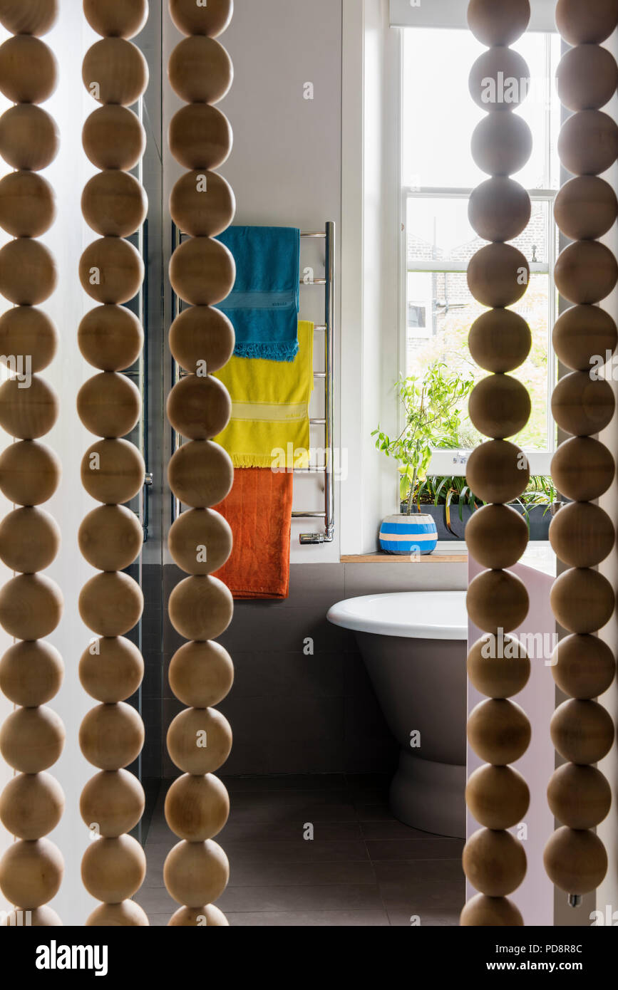 Oversized wooden beaded curtain with view to ensuite bathroom - Stock Image