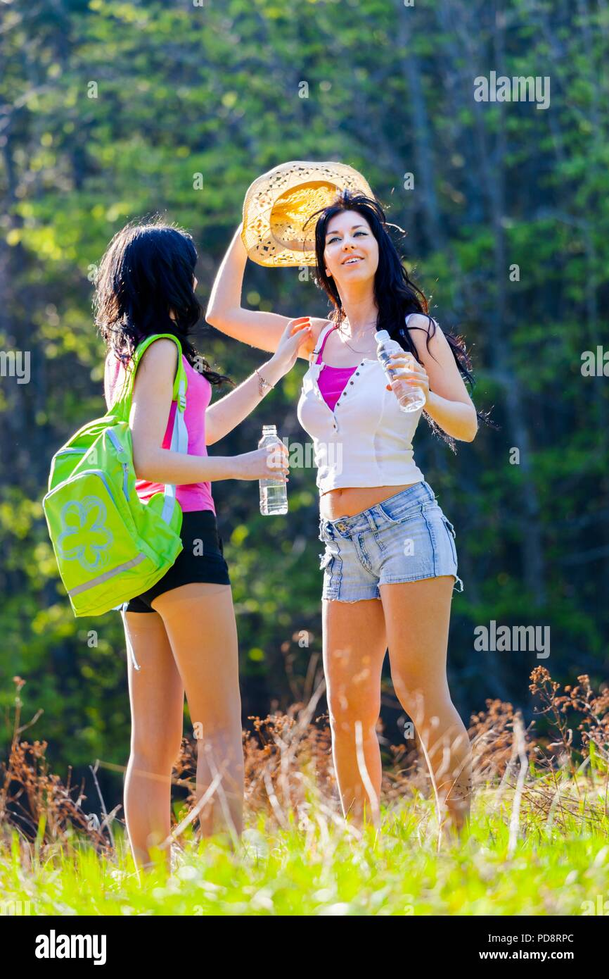 Two good pretty girlfriends in woodland trying straw-hat - Stock Image