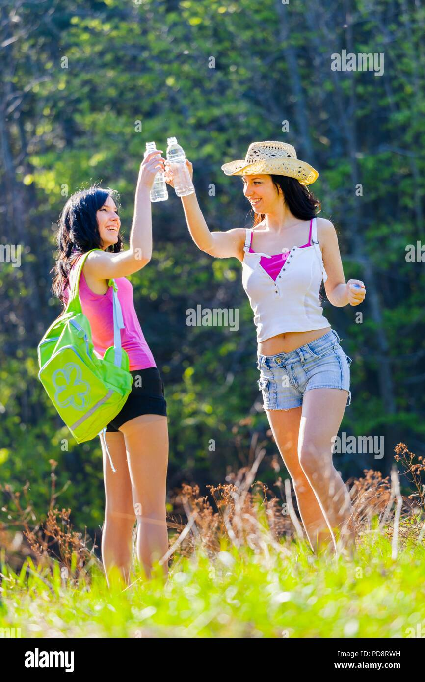Two good pretty girlfriends in woodland cheers happy and smiling - Stock Image