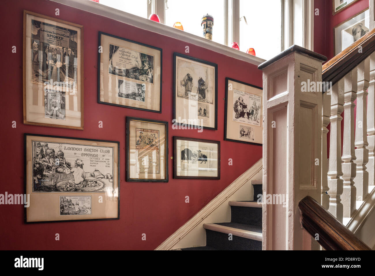 Old framed cartoons on the red staircase wall of the London Sketch Club - Stock Image